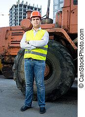 capataz, en, casco, posar, al lado de, excavadora, con, manos cruzadas