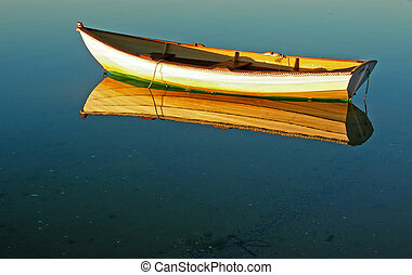 An old-fashioned dory casts a crisp image onto the calm waters of Stage Harbor at Chatham, Massachusetts.