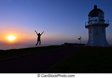 Cape Reinga Lighthouse - A woman jumps in the air during...