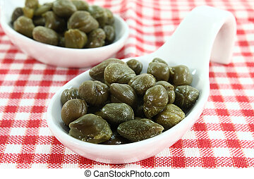 Capers - pickled caper berries on a white spoon