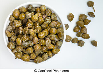 Capers with green leaves and flower on white background