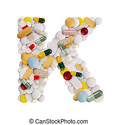 Capital letter K made of various colorful pills, capsules and tablets on isolated white background