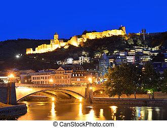 Capital of Georgia - Tbilisi at night against the dark blue sky