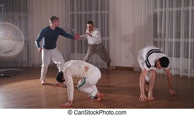 Capoeira. A group of smortsman training their skills. Mid...