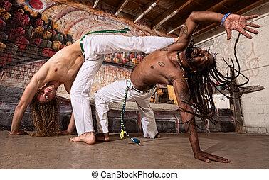 Capoeira Kicking - Pair of capoeira performers doing a...
