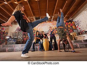 Capoeira Performers Kicking