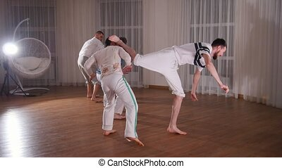 Capoeira. Sparring. A group of smortsman training their...