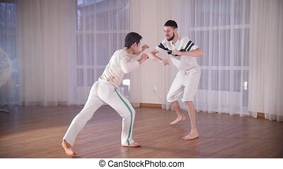 Capoeira. Two men training their skills. Kicking and...