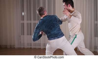 Capoeira. Two professional men training their material art...
