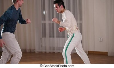 Capoeira. Two professional men training their skills. Mid...