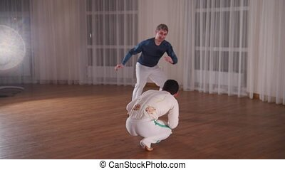 Capoeira. Two young men training in the studio at night. Mid...