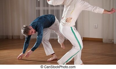 Capoeira. Two young men training in the studio. Mid shot