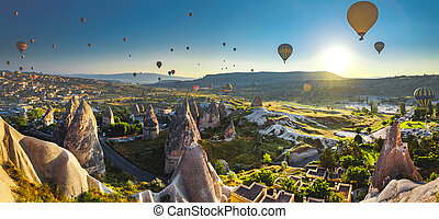Cappadocia valley at sunrise - Hot air balloon flying over...