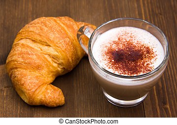 Cappuccino and croissant on wood