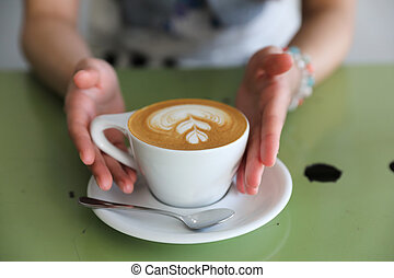 Cappuccino coffee with young woman hand