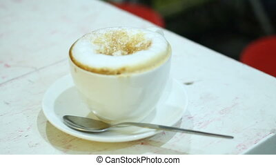 Cappuccino cup of coffee with sugar on a foam. Sweet hot beverage in white mug.