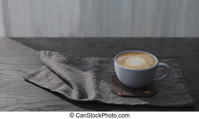 cappuccino in blue cup on black wood table