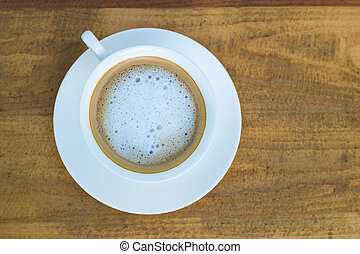 Cappuccino in white cup on wood background
