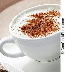 Cappuccino or latte coffee in cup with frothed milk and cookies