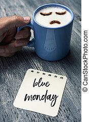 closeup of a note with the text blue Monday written in it on a gray rustic table and a young caucasian man with a blue cup of cappuccino with a sad face drawn with cocoa powder on its milk foam