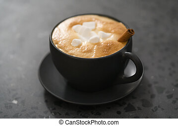 cappuccino with marshmallow and cinnamon in black cup on terrazzo surface
