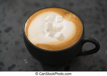cappuccino with marshmallow in black cup on terrazzo surface