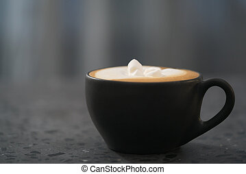 cappuccino with marshmallow in black cup on terrazzo surface with copy space