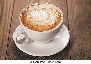 cappucciono with latte art on oak table