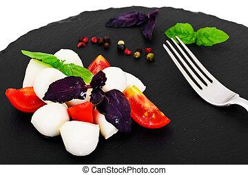 Caprese salad of tomatoes, basil, mozzarella, pepper