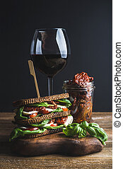 Caprese sandwich, glass of wine and dried tomatoes in jar