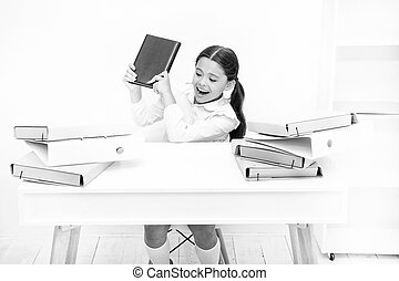 Capricious girl. Small girl raising book at folders. Angry girl hates reading book. Naughty child being noisy at school. Little child refusing to reading literacy. Schoolgirl having literature lesson