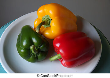 Several multicolored bell pepper capsicum vegetables on white plate