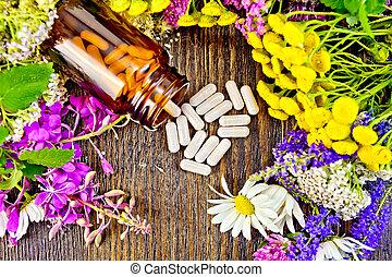 Capsules in brown jar with flowers on board top