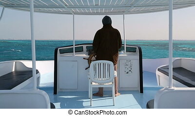 captain at controls on yacht in sea