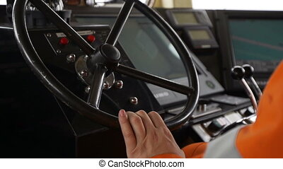 Captain at the helm of boat. Hands on steering wheel closeup