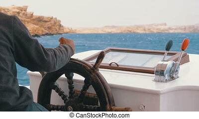 Captain at the Steering Wheel of a pleasure boat. Captain...