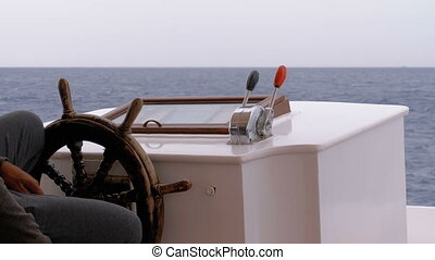 Captain at the Steering Wheel of a pleasure boat. Captain controls the sea yacht