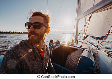 Captain of the yacht wearing sunglasses in a race on a river or sea at sunset