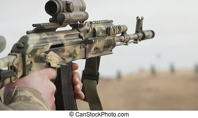 Captain shooting from AK 74 with an optical sight in a range in slow motion