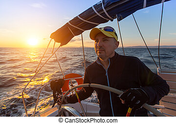 Captain steers the sailing yacht on the sea during sunset.