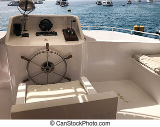 Captain's cabin on a ship, boat, cruise liner with a steering wheel, dashboard with a sea compass and instruments for control against the blue sea and ships under the sky.
