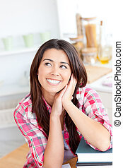 Captivating asian woman sitting in the kitchen with her books