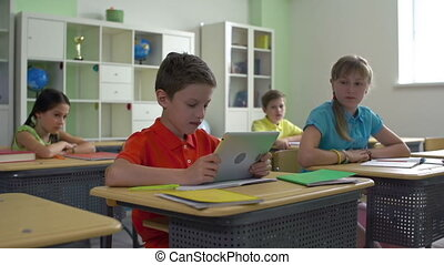 Captivating Video Game - Pupil playing on tablet in...