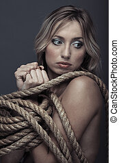Captivity - Suffering lady bonding by the rope. Studio ...