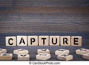 Capture word written on wood block. Dark wood background with texture