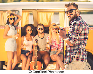 Capturing bright moments. Smiling young man holding retro styled camera and looking over shoulder while four young cheerful people sitting in retro minivan in the background