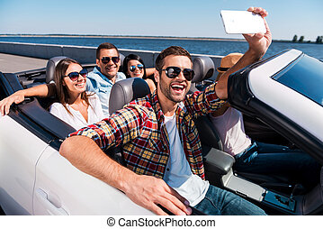 Capturing fun. Group of young happy people enjoying road trip in convertible and making selfie