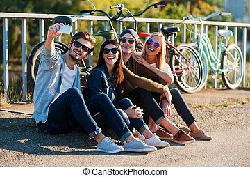 Capturing fun. Group of young smiling people bonding to each...