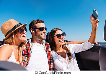 Capturing fun. Three young happy people enjoying road trip in convertible and making selfie