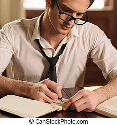Capturing his thoughts. Handsome young author sitting at the table and writing something in his sketchpad